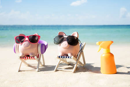 Close-up Of Piggybank With Modern Sunglasses And Headphone On Deck Chair On Sand At Beach