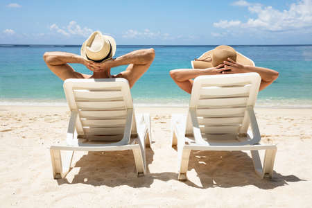 Rear View Of A Young Couple Wearing Hat Relaxing On Deck Chair On Beach Stockfoto