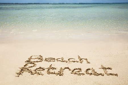Close-up Of Beach Retreat Text On The Sandy Beach Near The Idyllic Sea