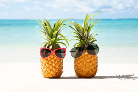 Two Pineapple With Red And Black Sunglasses On Sand At Beach