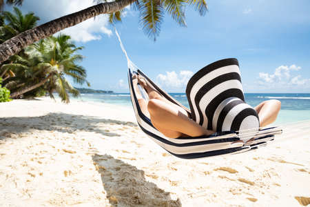 Woman In Striped Hat Relaxing On Hammock Over The Idyllic Beach In Summer Stockfoto