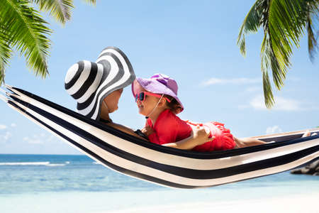 Mother And Daughter Lying On Striped Hammock Enjoying The Vacation Over The Sea At Beach