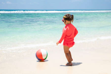 Toddler Girl Playing With Ball Near The Idyllic Seashore On Beach Stockfoto - 124799763