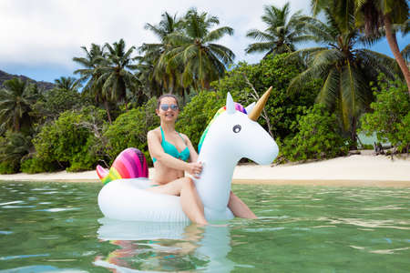 Portrait Of A Smiling Young Woman Sitting On Inflatable Unicorn Floating On Sea At Beach