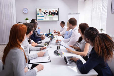 Group Of Businesspeople Having Video Conference With Another Business Team In Office Imagens