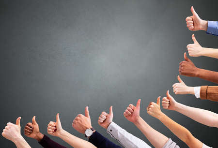 Close-up Of People's Hand Showing Thumb Up Sign Over Green Backdrop Stock Photo