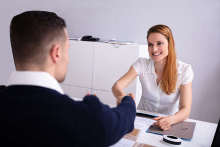 Smiling Businesswoman Shaking Hand With Her Colleague Over Desk At Workplace