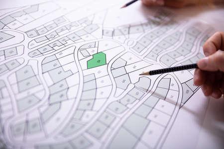 Zbliżenie ludzkiej ręki trzymającej ołówek nad papierową mapą katastru