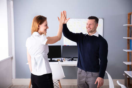 Smiling Male And Female Businesspeople Giving High Five At Workplace Imagens
