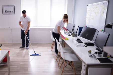 Two Smiling Young Janitor Cleaning The Desk And Mopping Floor In The Office