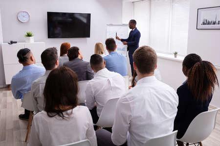 Retrato de apuesto joven empresario dando presentación a sus colegas sentados en una silla en la oficina Foto de archivo