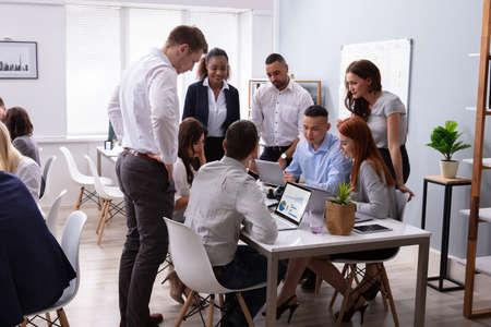Gruppo di giovani diversi uomini d'affari che lavorano e comunicano mentre sono seduti alla scrivania dell'ufficio