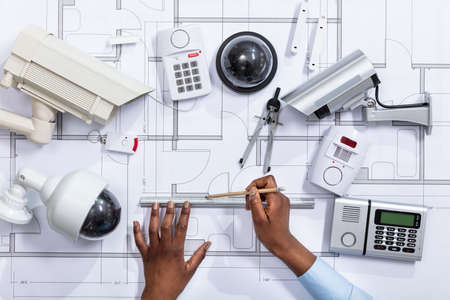 Close-up Of An Architect's Hand Drawing Blueprint Near Security Equipment