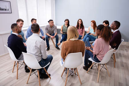 Giovani amici millenari multirazziali seduti in cerchio che hanno una discussione di gruppo
