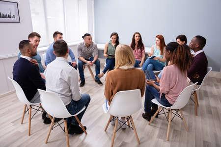 Jonge multiraciale duizendjarige vrienden zitten in een kring en hebben een groepsdiscussie