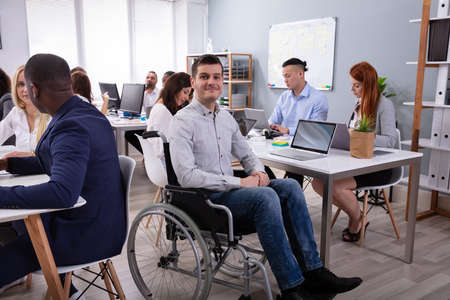Portrait Of A Disabled Businessman On Wheelchair At Office Фото со стока