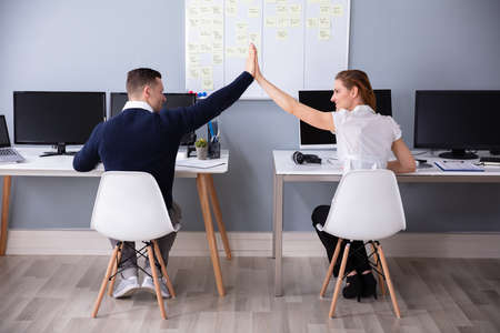 Rear View Of Businesspeople Sitting On Chair Giving High Five In Office