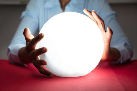 Close-up Of Fortuneteller's Hand Covering The Glowing Crystal Ball On Red Desk Stock Photo