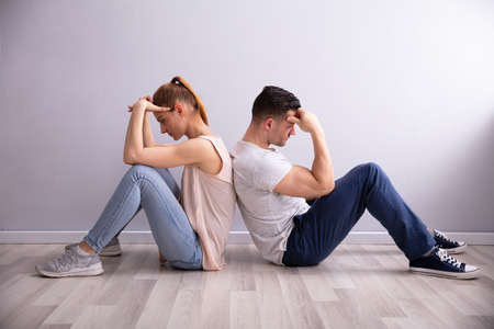 Sad Young Couple Sitting Back To Back On Floor At Home