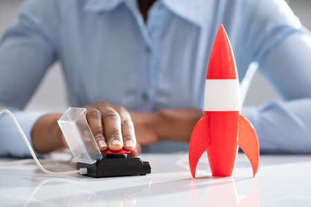 Businesswoman's Hand Launching Rocket By Pressing Red Button Imagens - 124601813