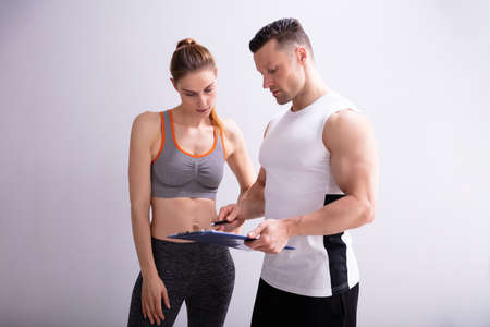 Young Trainer And Sporty Woman Discussing Her Progress At The Gym