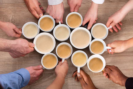 High Angle View Of Peoples Hand Holding Fresh Coffee Cups Against Wooden Background Фото со стока
