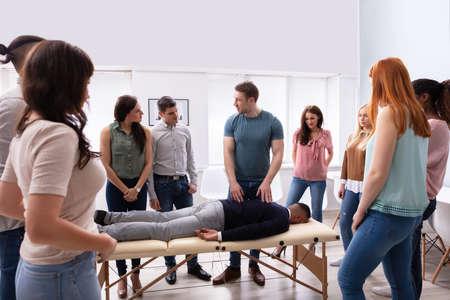Istruttore maschio che insegna la tecnica del massaggio a un gruppo di persone multietniche Archivio Fotografico