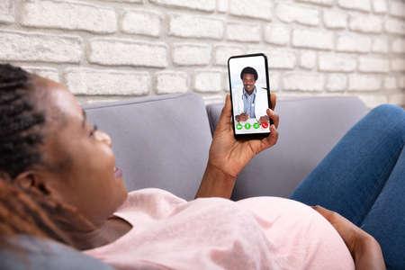 Close-up de mujer embarazada videollamada a su médico en el teléfono móvil