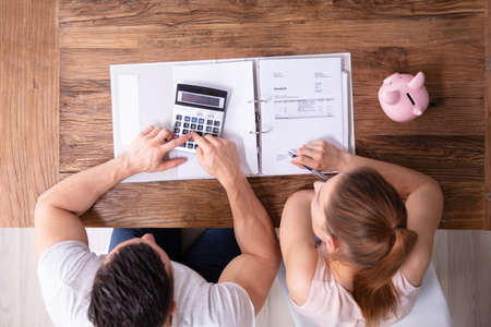 An Overhead View Of Couple Calculating Tax Invoice Using Calculator On Wooden Desk At Home