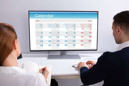 Two Businesspeople Looking At Calendar On Desktop Computer At Desk