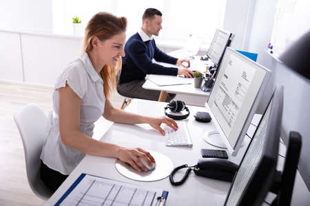 Smiling Young Businesswoman Checking Invoice On Computer At Workplace