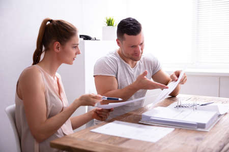 Young Couple Arguing About Expensive Invoice At Home