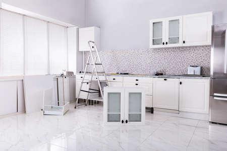 Installation des weißen Schranks mit Werkzeugen und Leiter im neuen modularen Haus