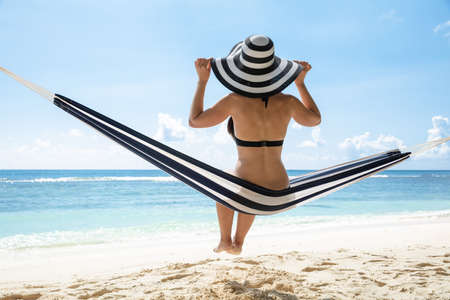 Side View Of A Young Woman In Bikini With Hat Sitting Over Hammock At Beach