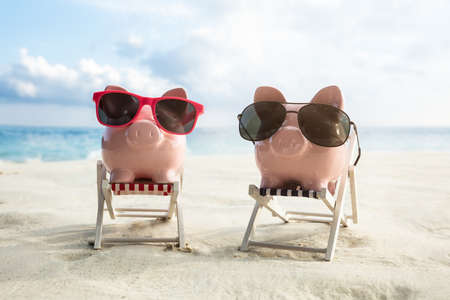 Sunglasses On Two Pink Piggybanks Over The Miniature Chairs On The Sandy Beach