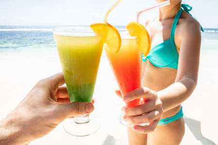 Young Woman In Bikini Toasting The Cocktail Glasses With Man's Hand At Beach During Summer Banco de Imagens - 124563155