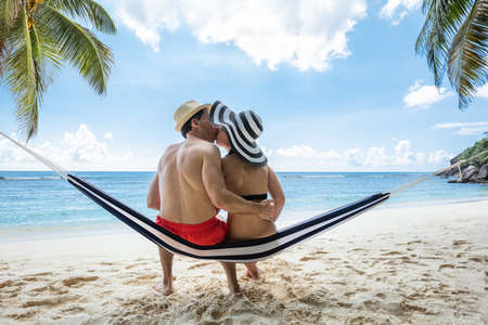 Rear View Of Young Couple Sitting On Hammock Kissing Near The Sea On Beach