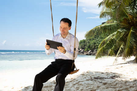 Man Sitting On Swing Using Digital Tablet At Sandy Beach Near The Idyllic Sea