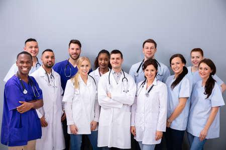 Porträt eines glücklichen gemischtrassigen Medienteams vor grauem Hintergrund