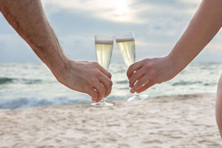 Close-up Of A Person Clinking Glasses Of Champagne In Hands At Beach Banco de Imagens - 124563962