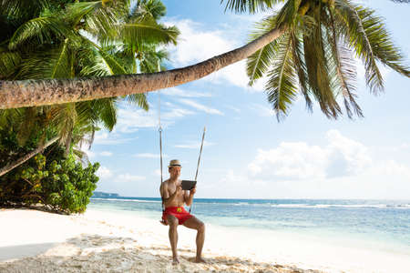 Man On Vacation Sitting Over The Swing Looking At Digital Tablet At Beach