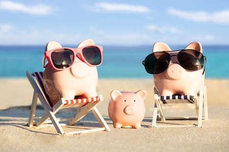 해변에서 모래에 선글라스와 핑크 돼지 저금통 가족의 전면 보기 스톡 콘텐츠