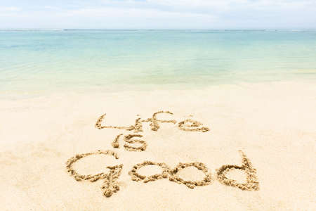 Close-up Of Life Is Good Word Written On The Sand At Idyllic Beach Фото со стока