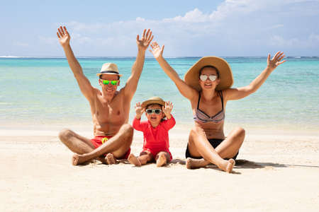 Happy Family Raising Their Hands Sitting On Sand Enjoying The Vacation At Beach