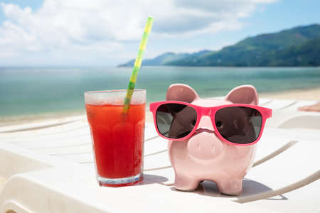 Close-up Of Fresh Juice And Piggybank With Sunglasses On White Deck Chair At Beach