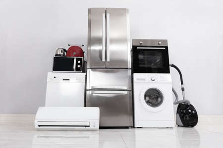 Set Of Household Kitchen Electronics Appliances On Reflective White Floor Against Wall