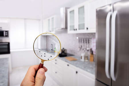 Close-up Of A Mans Hand Holding Magnifying Glass Over The Kitchen In Modular Kitchen Imagens