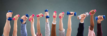 Group Of Man And Womans Hand Holding Dumbbells In A Row Against Green Background