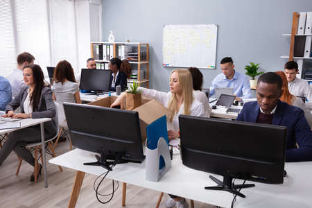 Businesspeople Looking At Smiling New Employee Unpacking Box With Personal Belongings In Office