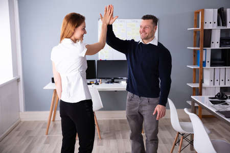 Smiling Male And Female Businesspeople Giving High Five At Workplace Stock Photo